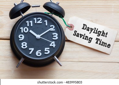 Daylight Saving Time words written on tag label with clock on wood background,Conceptual