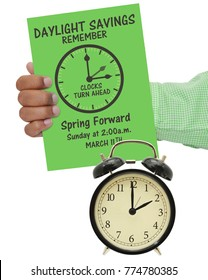 Daylight Savings Remember Spring Forward Clocks Turn Ahead at 2:00 am Sunday March 11 sign in hand over calendar on white background