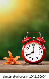 Daylight savings, spring forward concept - red alarm clock and flower - vertical image with blank, copy space