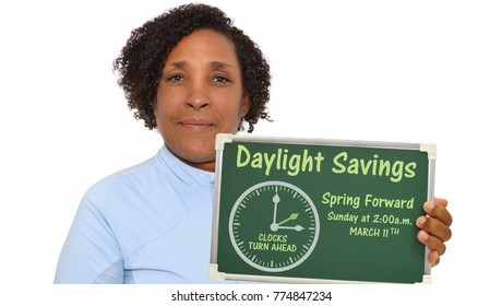 Daylight Savings Spring Forward Sunday at 2:00 a.m. March 11 chalkboard held by woman smiling looking at camera white background