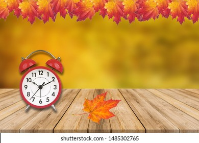 Daylight Savings Time Concept - Clock And Leaves On Wooden Table. Fall clock time move.