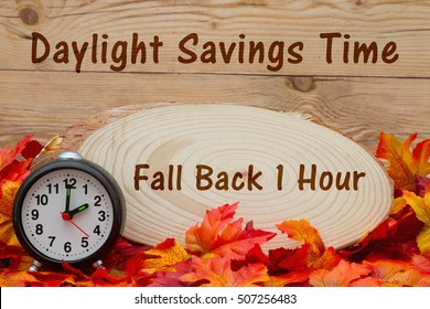 Daylight savings time message, Some fall leaves, an alarm clock and wood plaque on weathered wood with text Fall Back 1 hour