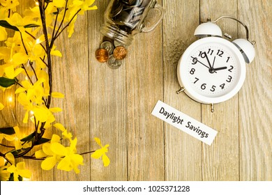 Daylight Savings Time Spring concept top down view with white clock and yellow forsythia flowers on wooden board