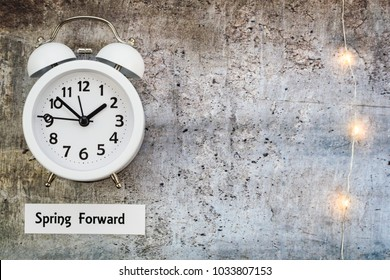 Daylight Savings Time Spring concept top down view with white clock and string lights