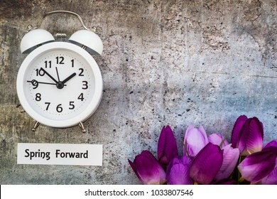 Daylight Savings Time Spring concept top down view with white clock and tulips