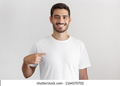 Daylight shot of smiling young man pointing at his blank white t-shirt with index finger, copy space for your ads, isolated on gray background