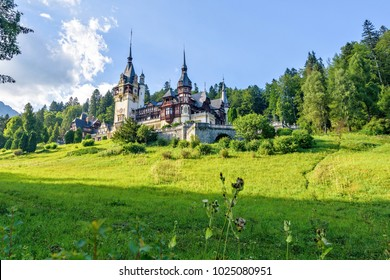 Daylight side far view to Peles castle front facade with hanging flag. Tree forest and bright blue clear sky on background. Romanian kings summer residence in Carpathian Mountains. Sinaia, Romania