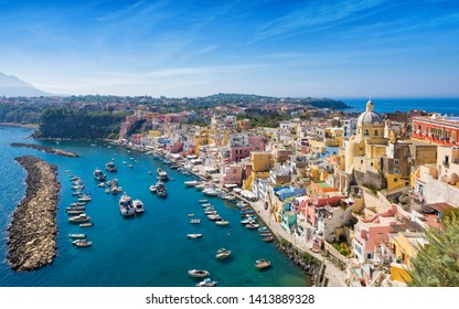 Daylight view of beautiful Procida in sunny summer day. Colorful houses, cafes and restaurants, fishing boats and yachts in Marina Corricella, clear blue sky and azure sea in Procida Island, Italy.