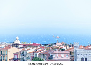 Daylight view to hotel buildings in shadow. Bright blue sea and clear sky on background. Helicopter flying above city. Negative copy space, place for text. Monte Carlo, Monaco