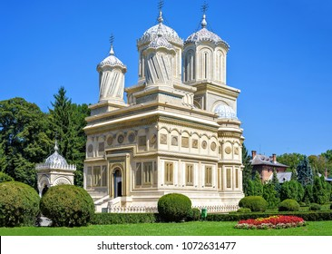 Daylight view to monastery garden park and cathedral on background. Green trees and bushes. Bright blue clear sky. Negative copy space, place for text. Curtea de Arges, Romania