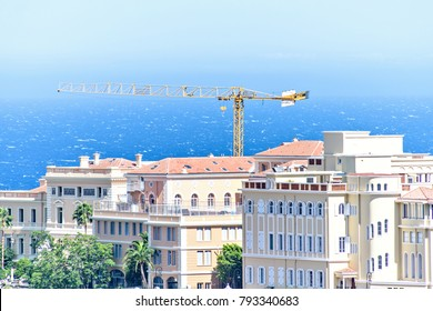 Daylight view to old town with oceanography museum, construction crane, green trees, apartments and buildings. Bright blue clear sky. Negative copy space, place for text. Monte Carlo, Monaco