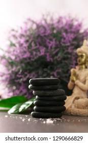 Dayspa massage stones. Spa and wellness setting. Basalt stones near calming water. Spa amd wellness products