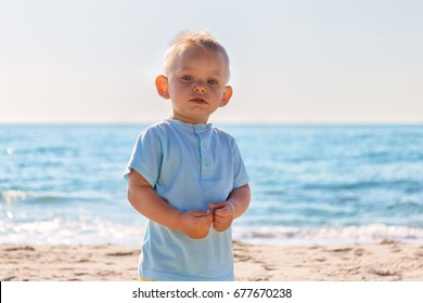 Day,summer,a boy of European descent ,blond-1.5 years .Standing on the beach and in the sky ,the blue sea and yellow sand.Puzzled and surprised look in the hands of shell.