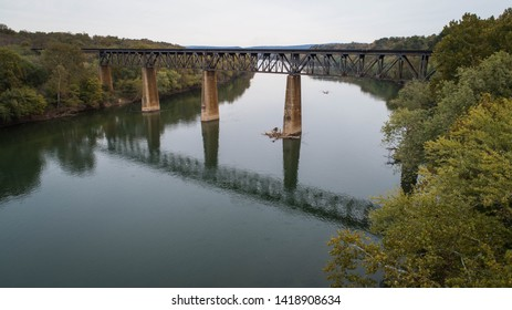 Daytime Aerial Landscape Photograph Looking Down at Reflections on Water and Rusted Steel Railroad Train Trestle Crossing Historic Potomac River in Maryland, USA
