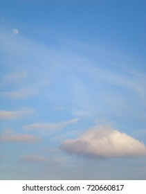 Daytime moon high in the blue sky surrounded by soft white clouds.