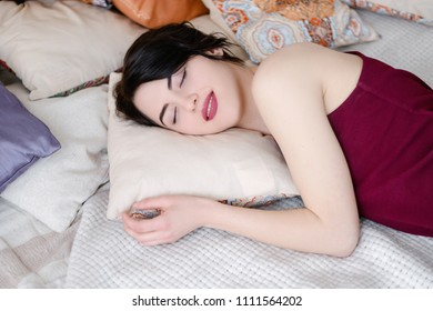 daytime nap. sweet dreams. woman smiling in her sleep. young beautiful girl lying in bed dreaming