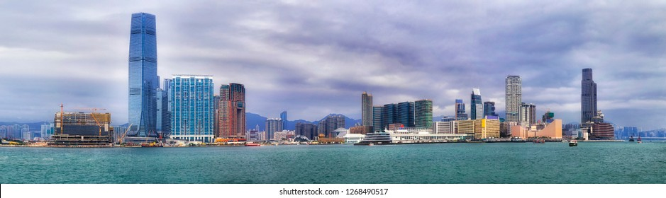 Daytime panorama of Kowloon and Thim Sha Tsui waterfront of Hong Kong across Victoria harbour around Star ferry pier and cultural centre with promenade and ferries.