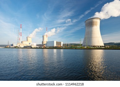 Daytime shot of a nuclear power plant at a river with blue sky and some clouds as well as reflection.