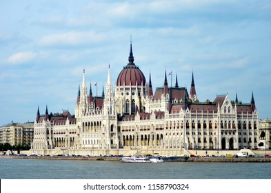 A daytime view of Budapest's Houses of Parliment, as seen from the water. Tour boats and buses have gathered on the wharf. The sky is blue with white clouds.