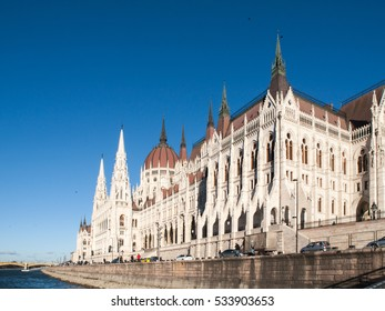 Daytime view of historical building of Hungarian Parliament, aka Orszaghaz, with typical symmetrical architecture and central dome on Danube River embankment in Budapest, Hungary, Europe. It is