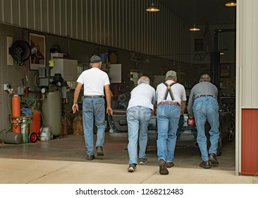 Dayton, Ohio - November 5, 2015: Four senior men push stalled car into garage for maintenance.