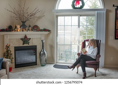 Dayton, Ohio, USA - December 12, 2018: Mature, blond woman sits in front of glass fireplace door looking down, smiling & reading a Christmas card.