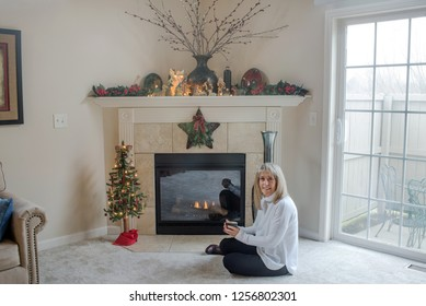 Dayton, Ohio, USA - December 12, 2018: Blond, mature woman sits in front of gas fireplace with cup in hand at Christmastime.