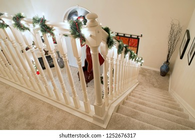 Dayton, Ohio, USA - December 5, 2018: Stair banister with Christmas decorations looking down on carpeted, open staircase with landing.