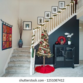 Dayton, Ohio, USA - December 6, 2018: Townhouse condominium open staircase with alpine Christmas tree against black accent wall.