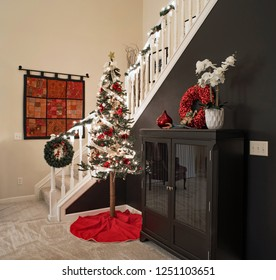 Dayton, Ohio, USA - December 6, 2018: Alpine Christmas tree in stairway corner with black accent wall at night.