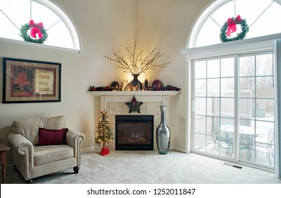 Dayton, Ohio, USA - December 6, 2018:  Contemporary living room corner fireplace with Christmas decorations & glass patio doors.