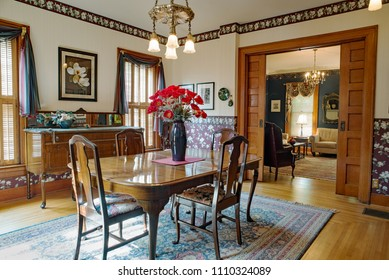 Dayton, Ohio, USA - June 10, 2018: Victorian dining room with wallpaper, high ceiling, silver chandelier, oriential rug & Queen Anne table, chairs & buffet in old home with pocket doors.