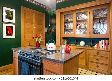 Dayton, Ohio, USA - June 18, 2018: Green kitchen with built-in china cabinet, center island and spice cupboard in an hundred-year-old house.