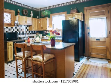 Dayton, Ohio, USA - June 18, 2018: Black & white tile & flooring accent a green Victorian kitchen in hundred-year-old home.