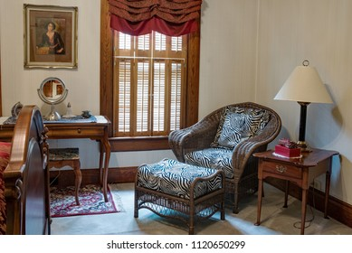 Dayton, Ohio, USA - June 25, 2018: Victorian bedroom sitting area or reading area with brown wicker chair & ottoman in one-hundred-year-old Victorian home.