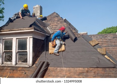 DAYTON, OHIO, USA - MAY 30, 2014: Migrant workers take on the dangerous task of restoring a steep, old, historic, roof.