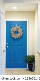 Dayton, Ohio, USA - November 19, 2018: Blue, interior, entrance door stands at end of short condominium hallway with potted fern & overhead lighting.