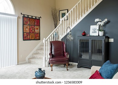 Dayton, Ohio, USA - November 19, 2018: Townhouse condominium living room with open staircase & black accent wall.