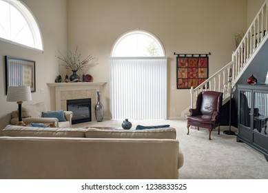Dayton, Ohio, USA - November 23, 2018: Condo living room in neutral colors with cathedral ceiling & arched windows.
