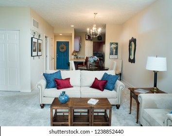 Dayton, Ohio, USA - November 23, 2018:  Direct view of contemporary living room arrangement in neutral tones with colorful pillows looking into dining area & kitchen.