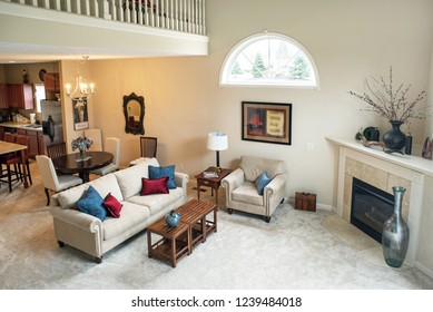 Dayton, Ohio, USA - November 23, 2018:  High view looking down into living room arrangement in open space condo in neutral tones with over-head loft area.