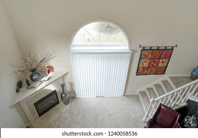 Dayton, Ohio, USA - November 23, 2018: Condo living room in neutral colors with cathedral ceiling & arched windows as seen from loft.