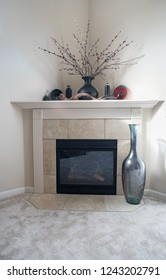 Dayton, Ohio, USA - November 23, 2018:  Contemporary, corner fireplace with tan tile and large glass bottle decor.