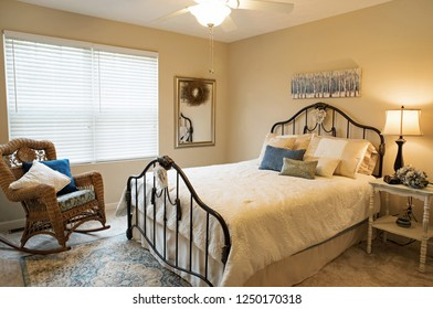 Dayton, Ohio, USA - October 14, 2018: Modern bedroom interior in neutral tones with old fashioned iron bed.