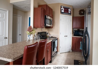 Dayton, Ohio, USA -September 28, 2018: Condo galley kitchen with cherry cabinets, counter with leather stools and walk-in corner pantry.