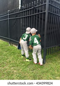 DAYTONA BEACH , FL - JUNE 9: Two young Little League players try to catch a glimpse of the minor-league players in the batting cage at the Jackie Robinson Stadium.