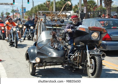 "DAYTONA BEACH, FL - MARCH 17:  A customized motorcycle towing a trailer cruises Main Street on St. Patrick's Day during ""Bike Week 2012"" in Daytona Beach, Florida."