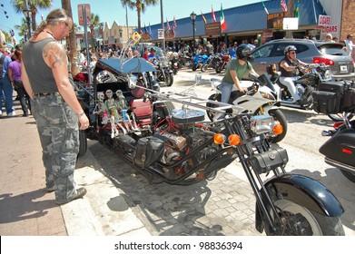 "DAYTONA BEACH, FL - MARCH 17:  Customized motorcycles line Main Street during ""Bike Week 2012"" in Daytona Beach, Florida."