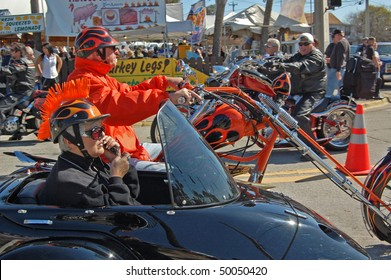 "DAYTONA BEACH, FL - MARCH 6: Older biker couple cruising down Main Street while woman talks on cell phone during ""Bike Week 2010"" in Daytona Beach, Florida."