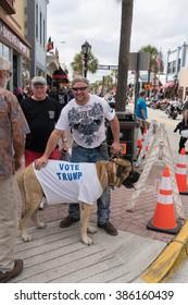 "Daytona Beach, Fl, USA - March 4, 2016: Man and his ""Vote Trump"" T-shirted dog at the 75th Anniversary of the Daytona Beach Bike Week."